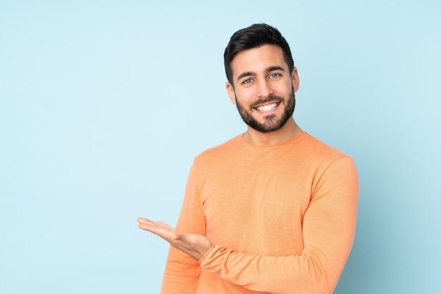 Kaukaski Przystojny Mężczyzna Przedstawia Pomysł Podczas Gdy Patrzejący Uśmiecha Się Nad Odosobnioną Błękit ścianą W Kierunku Premium Zdjęcia