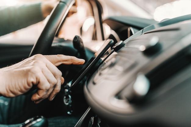 Kaukaski Starszy Mężczyzna Włącza Nawigację Na Mądrze Telefonie Podczas Gdy Siedzący W Jego Samochodzie. Premium Zdjęcia