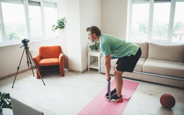 Kaukaski Trener Fitness Robi ćwiczenia Rozciągające Przed Kamerą Z Gumką W Odzieży Sportowej Premium Zdjęcia
