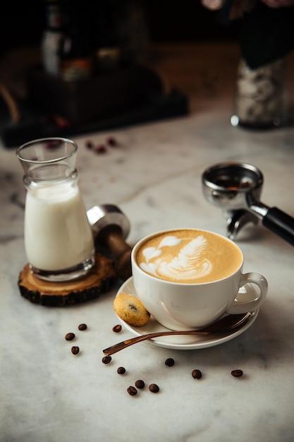 Kawa Cappuccino Na śniadanie Z Mlekiem I Ciastkami Na Białym Marmurowym Stole Premium Zdjęcia