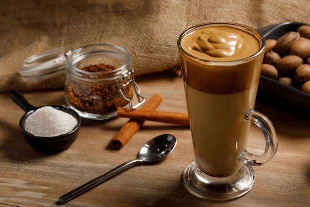 Kawa Dalgona - Koreański Kawowy Napój Na Drewnianym Tle. Kawa Rozpuszczalna Lub Espresso W Proszku Ubite Z Cukrem I Gorącą Wodą. Mrożona Bita Kawa Z Dalgony. Premium Zdjęcia