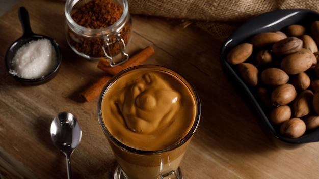 Kawa Dalgona - Koreański Kawowy Napój Na Drewnianym Tle. Kawa Rozpuszczalna Lub Espresso W Proszku Ubite Z Cukrem I Gorącą Wodą. Mrożona Koncepcja Bitej Kawy Dalgona. Widok Z Góry. Premium Zdjęcia