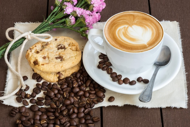 Kawa i fioletowy kwiat witn fasoli i białego szkła, naczynia, tkaniny na brązowy drewniany Premium Zdjęcia