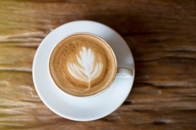 Kawa w białej filiżance na drewnianym stole Premium Zdjęcia
