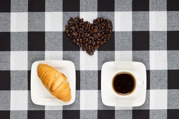 Kawa w białej filiżance, rogalik i serce z ziaren kawy Premium Zdjęcia