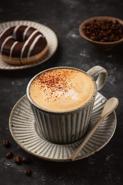 Kawa W Filiżance Z Pączkiem I Ziarnami Kawy Premium Zdjęcia