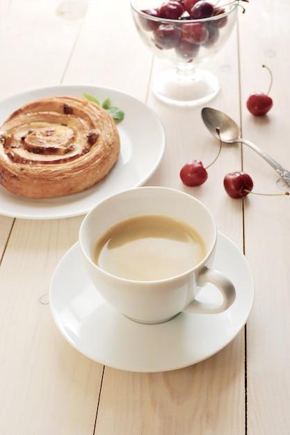 Kawa w kubku, babeczka z wiśniami cynamonowymi na białym tle Premium Zdjęcia