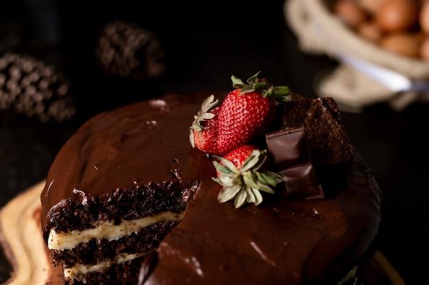 Kawałek Domowego Ciasta Czekoladowego Ze Smaczną Truskawką Na Stole Premium Zdjęcia