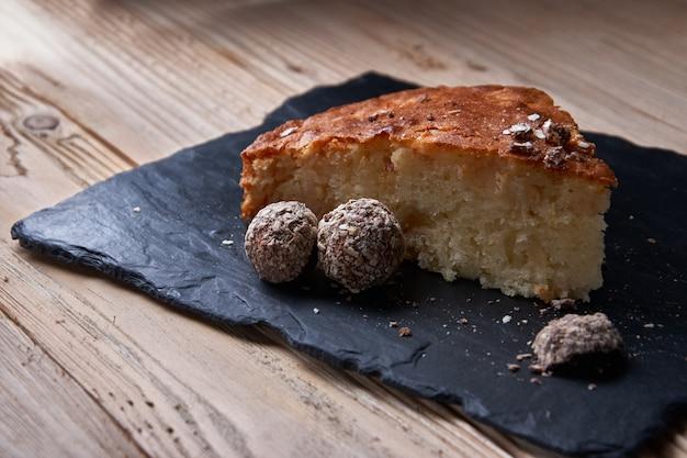 Kawałek Szarlotki Z Startą Czekoladą W Pobliżu Czekoladowych Cukierków Truflowych. Premium Zdjęcia