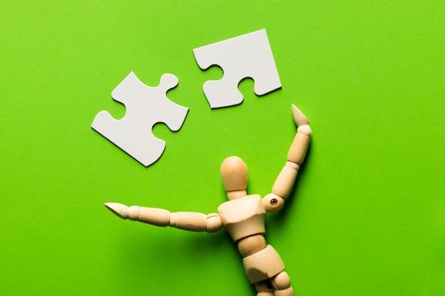 Kawałek Układanki Z Drewnianą Figurą Człowieka Na Zielonym Tle Darmowe Zdjęcia