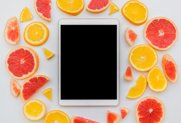 Kawałki owoców cytrusowych wokół cyfrowego tabletu Darmowe Zdjęcia