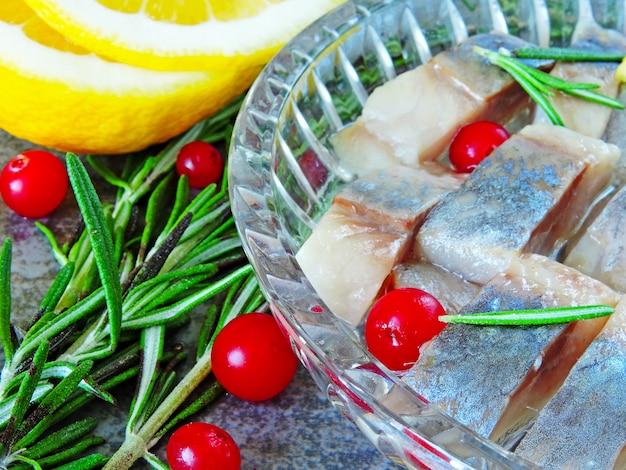 Kawałki śledzia W Kryształowym Naczyniu. żurawina, Cytryna I Rozmaryn. śledź Norweski Premium Zdjęcia