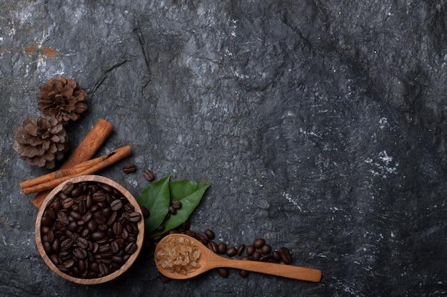 Kawowe fasole w drewnianej filiżance, sośnie i zieleni liścia cukierze na drewnianej łyżce na czerni drylują tło Premium Zdjęcia