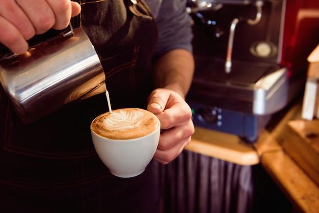 Kawowy latte barista robi wzorowi w filiżance sklep z kawą. Premium Zdjęcia