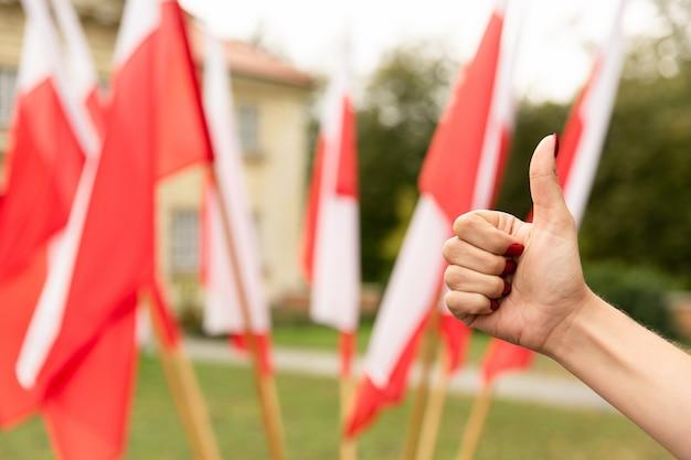Kciuk W Górę Gest Z Flagami Polski Za Premium Zdjęcia