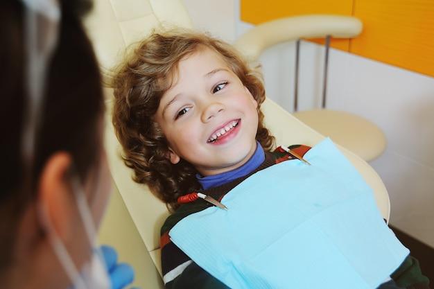 Kędzierzawe dziecko oddaje się i grymasuje na fotelu dentystycznym Premium Zdjęcia