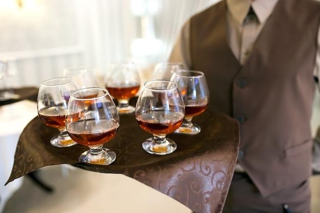 Kelner z tacą wita gości, napełnia kieliszki koniaku Premium Zdjęcia
