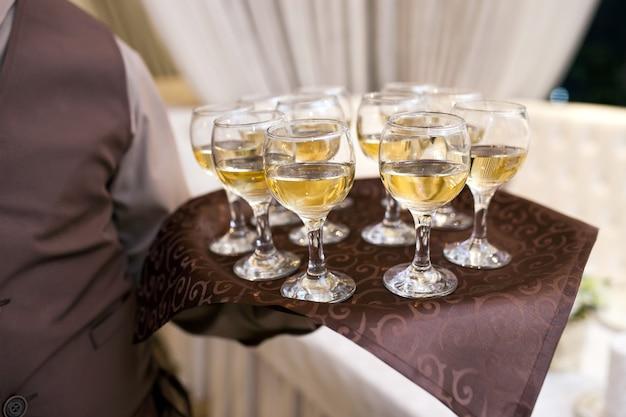 Kelner z tacą wita gości, napełnia kieliszki wina Premium Zdjęcia