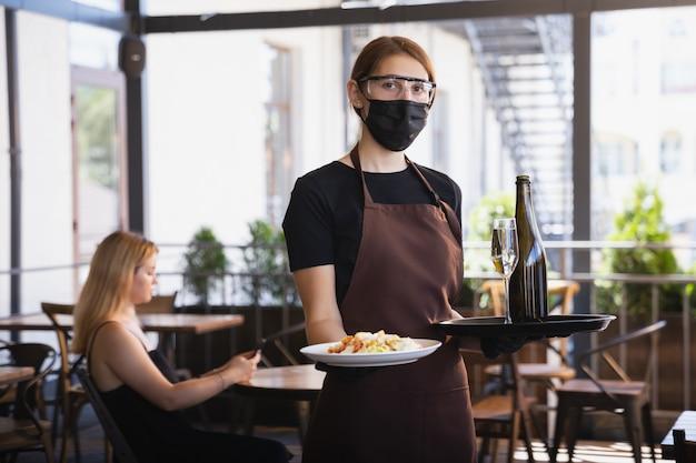 Kelnerka Pracuje W Restauracji W Masce Medycznej, Rękawiczkach Podczas Pandemii Koronawirusa Darmowe Zdjęcia
