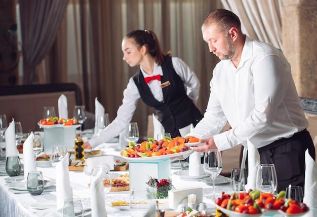 Kelnerzy serwujący stolik w restauracji przygotowujący się do przyjęcia gości. Premium Zdjęcia