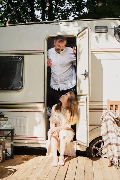 Kemping I Podróże. Szczęśliwa Para Relaks Na świeżym Powietrzu W Pobliżu Przyczepy Mężczyzna I Kobieta Na Ich Podróż Premium Zdjęcia