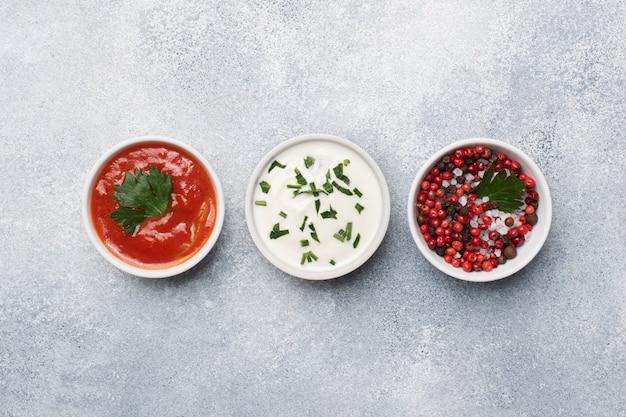 Ketchup Majonez Zielony Przyprawy Pieprz Sól W Talerzach Na Szarym Betonowym Stole Z Miejsca Kopiowania. Premium Zdjęcia