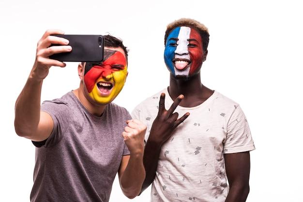 Kibice Kibiców Z Pomalowaną Twarzą Reprezentacji Francji I Niemiec Robią Selfie Na Białym Tle Darmowe Zdjęcia