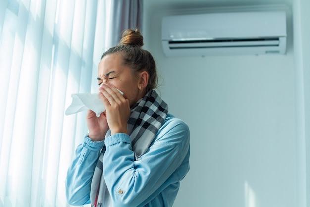 Kichająca Kobieta Złapała Przeziębienie Z Klimatyzatora W Domu. Choroba Odżywiająca Premium Zdjęcia