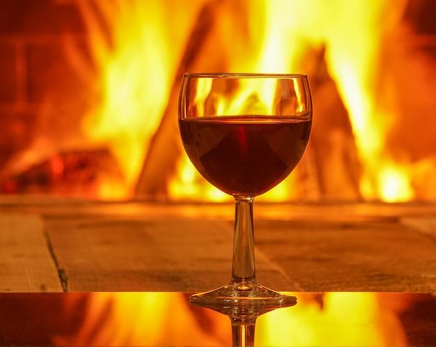 Kieliszek czerwonego wina na przytulny kominek Premium Zdjęcia