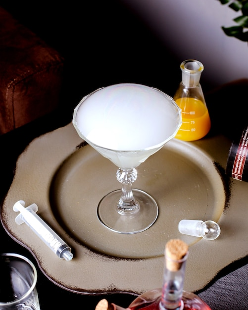 Kieliszek Martini Z Wędzonym Koktajlem Umieszczony Obok Igły I Stożkowa Kolba Z Sokiem Pomarańczowym Darmowe Zdjęcia
