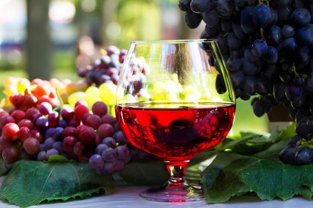Kieliszek Wina I Kiść Winogron. Czerwone Wino W Szklance Premium Zdjęcia