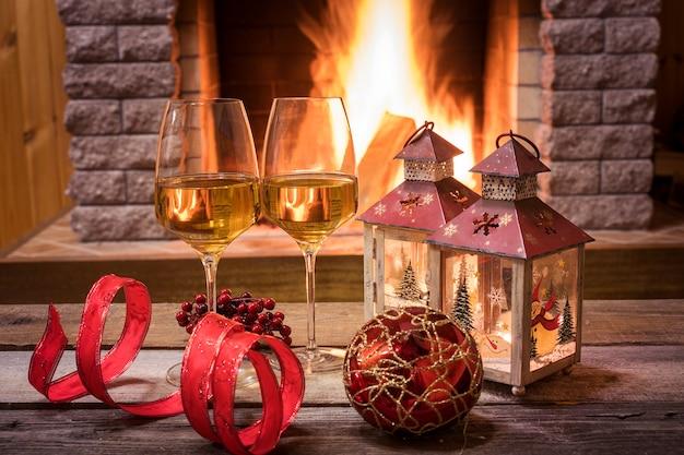 Kieliszki wina i świece przy kominku Premium Zdjęcia