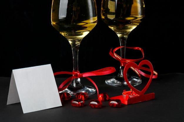 Kieliszki Z Szampanem Przewiązane Czerwoną Wstążką, Kartka Okolicznościowa I świecznik W Kształcie Serca Premium Zdjęcia