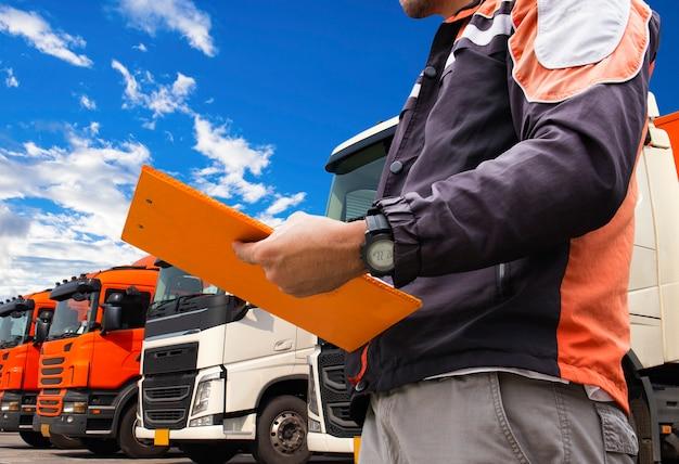 Kierowca ciężarówki trzyma schowek z inspekcją ciężarówek. Premium Zdjęcia