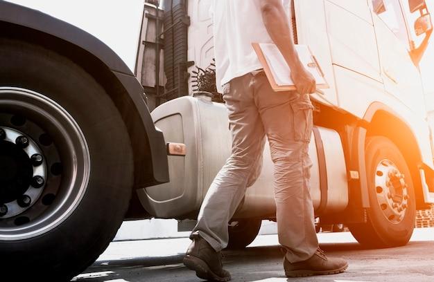 Kierowca Ciężarówki Trzymający Notatnik, Sprawdzający Codziennie Pół Ciężarówka Bezpieczeństwa, Transport Towarowy. Premium Zdjęcia
