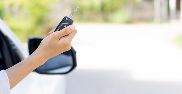 Kierowca szofera ręka trzyma kluczyk i pokazuje za oknem Premium Zdjęcia