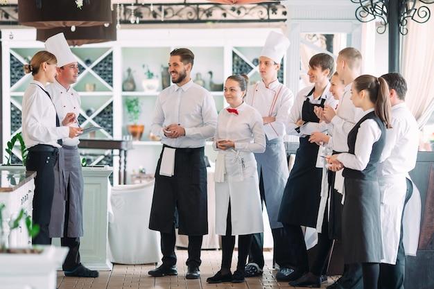 Kierownik restauracji i jego personel na tarasie. interakcja z szefem kuchni w restauracji. Premium Zdjęcia
