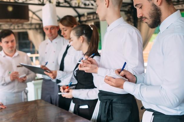 Kierownik Restauracji I Jego Pracownicy Na Tarasie, Wchodząc W Interakcje Z Szefem Kuchni W Restauracji, Premium Zdjęcia