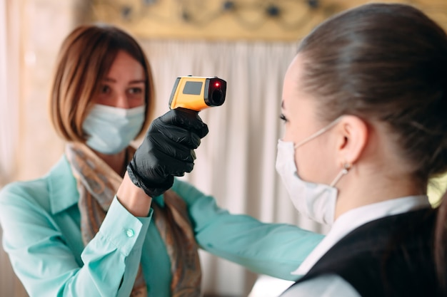 Kierownik Restauracji Lub Hotelu Sprawdza Temperaturę Ciała Personelu Za Pomocą Urządzenia Do Obrazowania Termicznego. Premium Zdjęcia