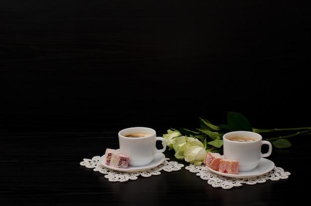 Kilka Filiżanek Kawy Z Mlekiem, Turkish Delight, Bukiet Białych Róż Na Czarnym Tle. Miejsce Na Tekst Premium Zdjęcia