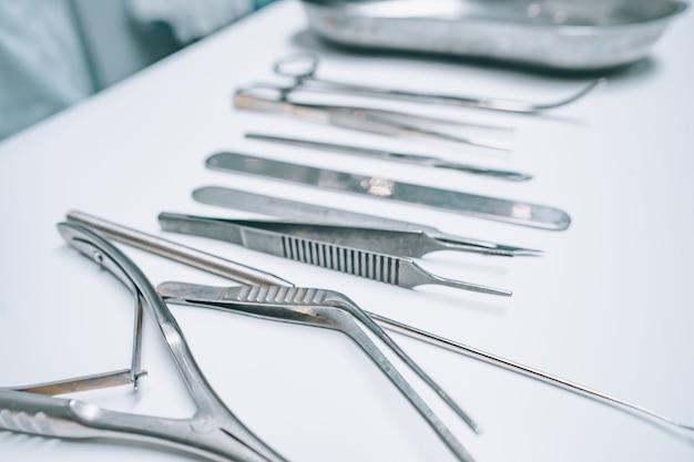 Kilka Instrumentów Chirurgicznych Leży Na Białym Stole Darmowe Zdjęcia