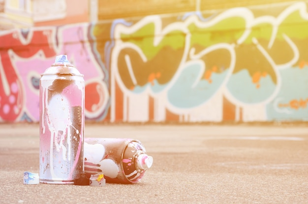 Kilka Używanych Puszek Z Różową I Białą Farbą W Pobliżu Pomalowanej ściany W Kolorowe Rysunki Graffiti Premium Zdjęcia