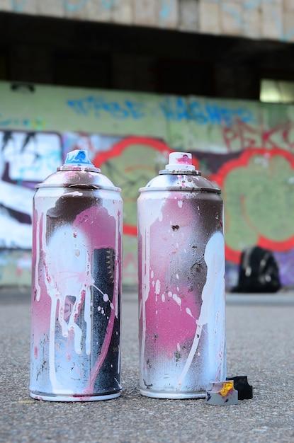 Kilka Zużytych Puszek Z Różową I Białą Farbą Oraz Nakrętki Do Natryskiwania Farby Pod Ciśnieniem Znajdują Się Na Asfalcie W Pobliżu Pomalowanej ściany Na Kolorowych Rysunkach Graffiti Premium Zdjęcia