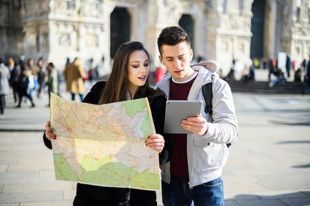 Kilku Turystów W Mieście Patrząc Na Mapę I Dyskutując O Kolejnym Celu Premium Zdjęcia