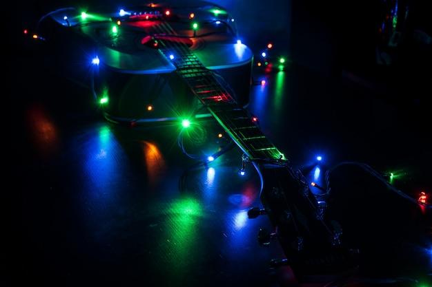 Klasyczna gitara akustyczna w świątecznych lampkach świątecznych w pamięci muzyki Premium Zdjęcia