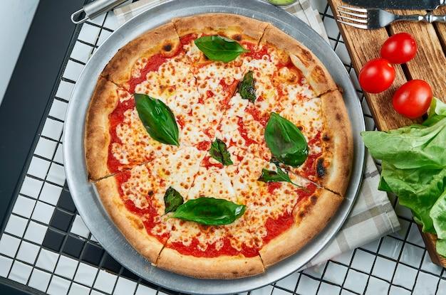 Klasyczna Pizza Margarita Z Mozzarellą, Pomidorami I Bazylią. Włoska Pizza W Składzie Z Składnikami Na Białym Stole. Widok Z Góry. Jedzenie Leżało Płasko Premium Zdjęcia