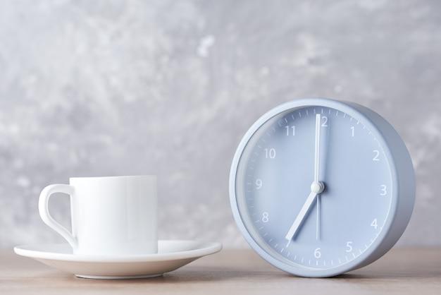 Klasyczny Budzik I Biała Filiżanka Kawy Na Szarym Premium Zdjęcia