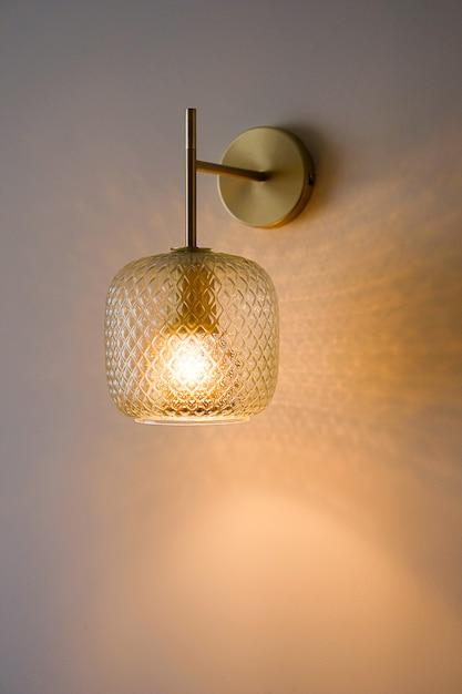 Klasyczny Kryształowy Kinkiet Lub Lampa Na ścianie, Na Tle Tapety Z Włączonym światłem. Skopiuj Miejsce Na Tekst. Selektywne Ustawianie Ostrości. Premium Zdjęcia