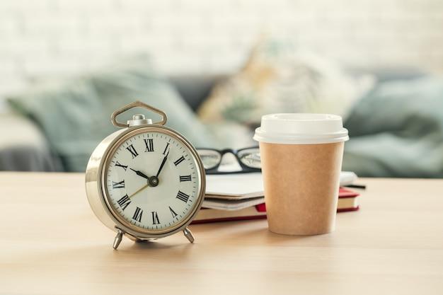 Klasyczny rocznika budzik, filiżanka kawy na drewnianym tle i Premium Zdjęcia