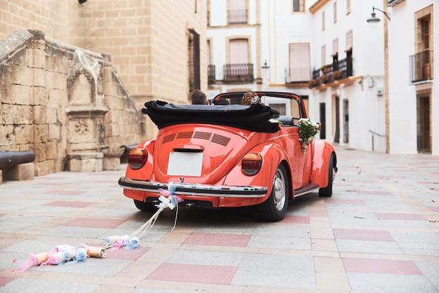 Klasyczny samochód retro czerwony ślub i nowożeńcy wewnątrz. Premium Zdjęcia